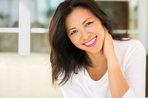 Middle Age Asian Woman Smiling from good visit to Pine Belt Periodontics